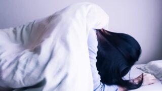 布団から起き上がれず寝込んでいる女性